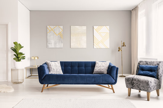 A modern living room interior of a luxurious hotel apartment with a designer couch, an armchair and art decorations. Real photo.