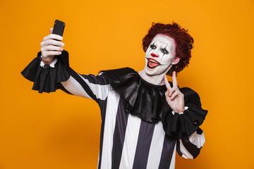 Smiling man clown making selfie on smartphone