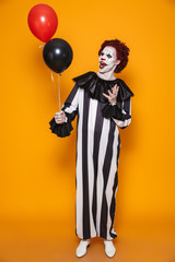 Cheerful man clown holding air balloons isolated