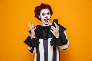 Surprised man clown using smartphone isolated