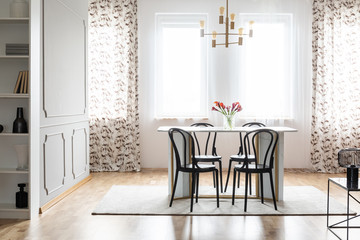 Real photo of a cozy dining room interior with patterned curtains, table, chairs and wall molding