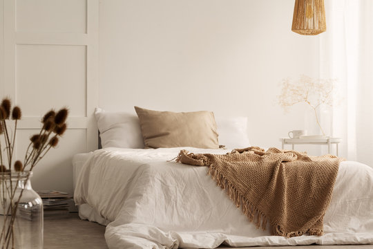 Flowers and lamp in white natural bedroom interior with blanket and pillows on bed. Real photo