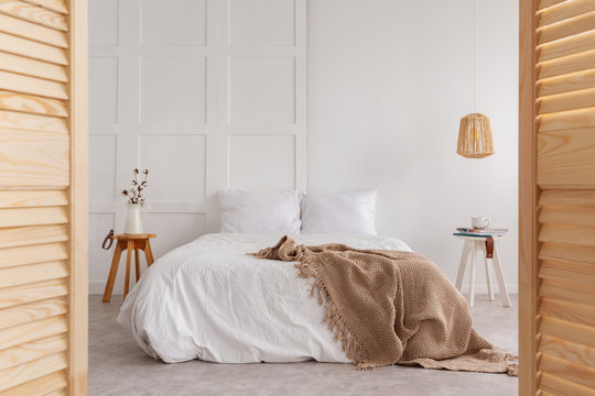 Wooden door and lamp in white bedroom interior with blanket on bed and flowers on table. Real photo