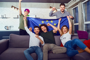 A group of friends with a European flag at a party. Friends celebrate the day of Europe.