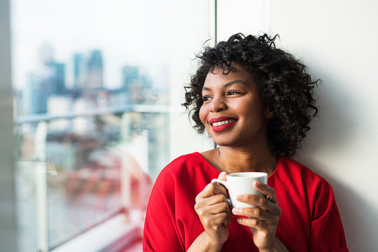 A close-up of a woman standing by the window holding coffee cup.
