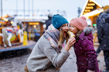 Young mother and daughter eating white chocolate covered fruits on skewer on traditional German Christmas market