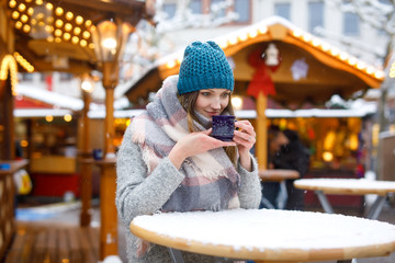 woman drinking hot punch on German Christmas market.