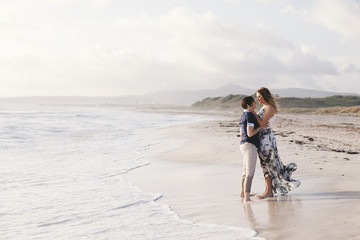 Young couple in love hug each other on the deserted beach on a summer evening