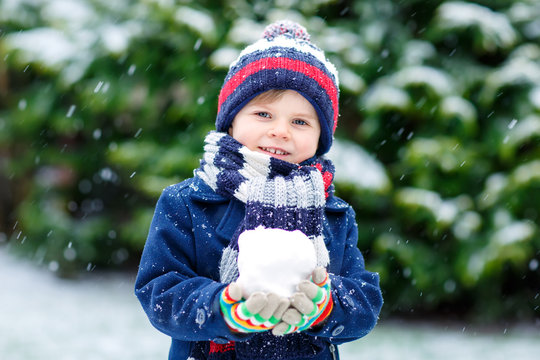 Cute little funny kid boy in colorful winter fashion clothes having fun and playing with snow, outdoors during snowfall