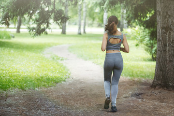 Young woman jogging down a path in a green park.