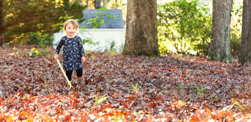 Toddler girl raking leaves on the ground in autumn