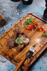 Grilled ribs served with sauce on wooden chopping board