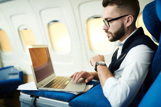 Side view portrait  of handsome businessman using laptop while working in plane during long first class flight, copy space