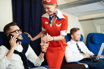 Portrait of smiling flight attendant serving glass sparkling water to handsome businessman enjoying first class trip, copy space Wall mural