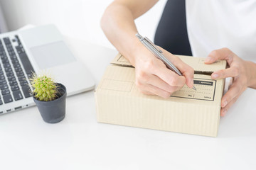 hands of woman writing on cardboard box at table, working at home concept, online marketing packaging box and delivery.
