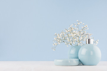 Light pastel blue ceramic acessories for bath  - bowl, vase, soap dispenser, flowers on white wood table. Decor for bathroom interior.