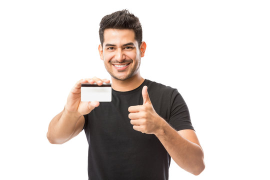 Smiling Young Man Holding Credit Card While Gesturing Thumbs Up