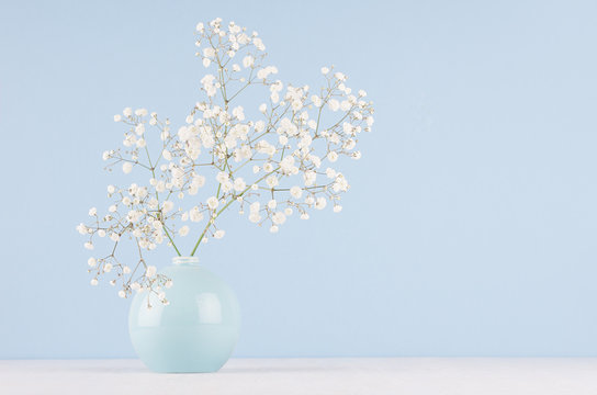Spring bouquet of white small fluffy flowers in blue smooth circle ceramic vase on soft white wood table and pastel blue wall.