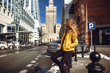 A young European woman, traveling, with long blond hair, wearing a yellow jacket, yellow sunglasses walking down the city center street, street shooting. Even light. Wall mural