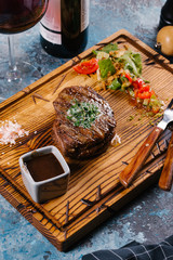 Fresh medium raw steak served with vegetable salad on wooden chopping board