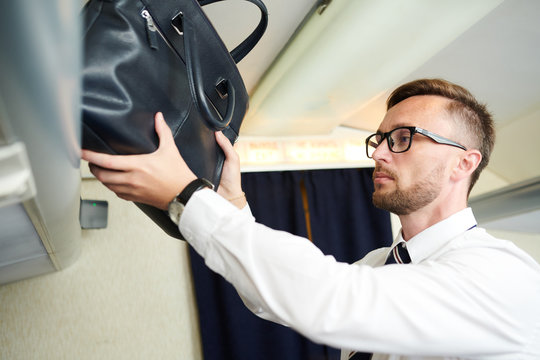Portrait of handsome businessman taking leather bag from luggage compartment in plane, copy space