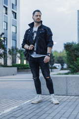 Young attractive man in black jeans jacket standing on cityscape background.