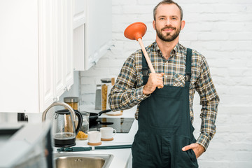 cheerful handsome plumber holding plunger on shoulder and looking at camera in kitchen