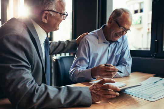 Smiling senior businessmen working together at cafe