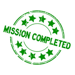 Grunge green mission completed with star icon round rubber seal stamp on white background