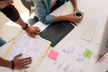 Business partners working on architecture plans in office