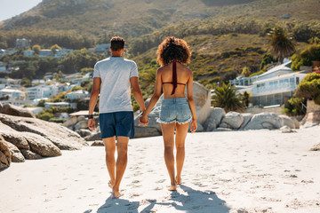 Romantic couple walking on sand at the beach