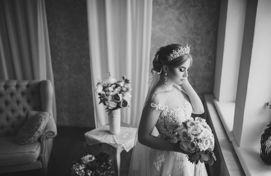 A beautiful bride with a bouquet in her hands is standing by the window. Blonde in a lace dress. Precious jewelry of the bride. Black and white photography, monochrome.