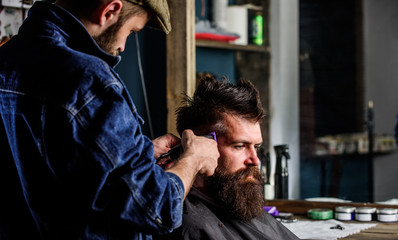 Barber with clipper trimming hair on temple of client. Hipster client getting haircut. Hipster lifestyle concept. Barber with hair clipper works on hairstyle for bearded man barbershop background