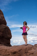 Attractive fit young woman photographer stands on top of a red rock formation in Arches National Park against a blue sky