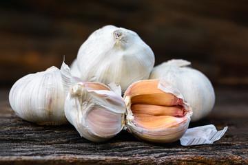 Garlic or Allium sativum L., white spices on brown woodden.