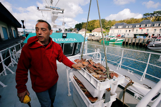 Thierry Lefrancois, captain of Thierisa trawler unloads boxes of scallops on the harbour of Port-en-Bessin