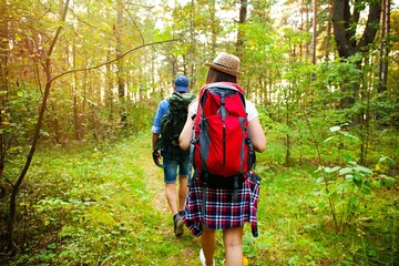 Tough route. Beautiful young couple hiking together in the woods while enjoying their journey.