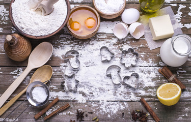 The cookie molds and ingredients for preparing Christmas homemade biscuits on a wooden table.