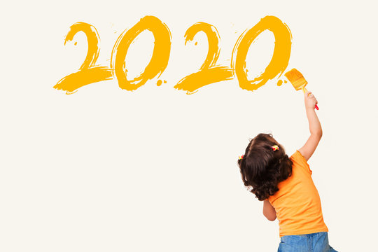 Cute little girl drawing new year 2020 with painting brush on wall background