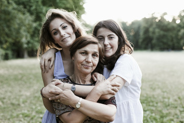 Mother and daughters embrace in a park at sunset on a summer evening