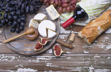 The set of fresh fruits- figs, grape, homemade cheese, red wine bottle, honey, white bread on a wooden background.