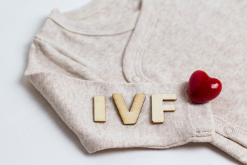 Baby clothes with wooden text IVF and heart. Concept - IVF, in vitro fertilization. Waiting for baby, pregnant