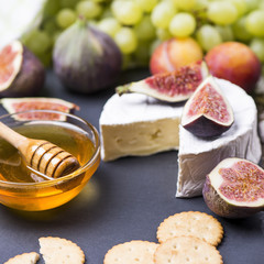 Soft cheese with fresh fruits - figs, grape, plums, honey, cookie cracker on a wooden background.