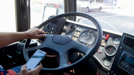 Closeup photo of truck driver typing on smartphone while driving. Danger in transport. Irresponsible driver