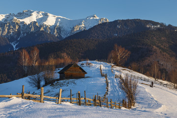 Alpine scenery with rustic wooden cottage and snow capped ridge of the Bucegi mountains in the sunset light in a cold winter evening, in Bran, Romania.