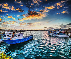 Boats in Alghero harbor at sunset