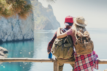 Couple Hikers with backpacks relaxing and enjoy the sea view. Traveling along mountains and coast, freedom and active lifestyle concept.