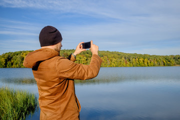 young bearded man in hat on the background of the lake takes a picture of nature on the phone