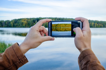 Men's hands hold the phone and take pictures of the autumn landscape on the lake