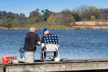 Two old men sitting on a dock, fishing. One man is helping the other with something. Concepts of recreation, vacation, friendship, summer